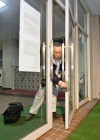 最後の避難所の旧埼玉県立騎西高校から町民が退去し、ドアを施錠する福島県双葉町の関係者(27日夜、埼玉県加須市)=共同