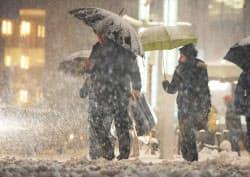 降りしきる雪の中を歩く人たち(8日夜、東京・銀座)
