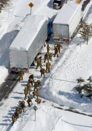 大雪のため大型トラックが動けなくなり、除雪作業に当たる自衛隊員ら(16日、長野県軽井沢町)=共同