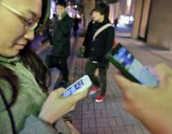 スマートフォンを手にする学生(26日、東京都千代田区)