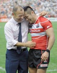 2013年6月、ウェールズ代表とのテストマッチに快勝し、広瀬主将(右、当時)と抱き合って喜ぶジョーンズ・ヘッドコーチ=共同