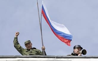 19日、ウクライナ南部セバストポリのウクライナ海軍基地の屋上でロシア国旗を掲げる男性=ロイター