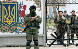 クリミア半島の中心都市シンフェロポリに近い海軍基地。ウクライナの国章が描かれた門の前にロシア兵とみられる覆面の兵士が立つ(19日)=共同