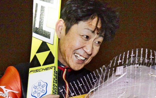 引退試合となるジャンプ国内最終戦を10位で終え、花束を手に笑顔の岡部孝信(22日、大倉山)=共同
