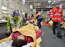 日米共同統合防災訓練で、護衛艦内で治療の手順を確認する災害派遣医療チーム=7日午後、高知県土佐市沖