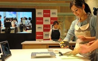 NTTドコモとABCクッキングスタジオが協力して実施した東京と香港をネットで結ぶライブ料理教室(中央奥が講師)