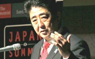 シンポジウムで講演する安倍首相(17日午前、東京都内のホテル)=共同