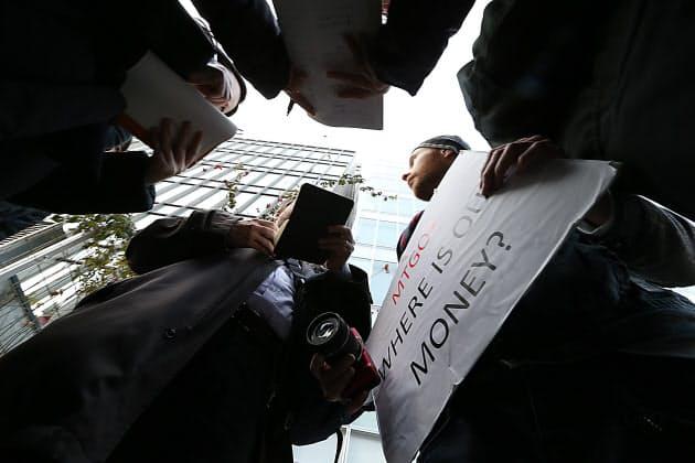 マウントゴックスの前で報道陣の質問に答える英国在住の男性(右。2月26日、東京・渋谷)。現在のレートで約1500万円を預けていたが引き出せないため来日したという