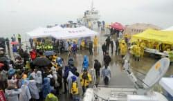 18日、旅客船沈没事故から3日目を迎えた韓国・珍島の漁港に集まった関係者ら=共同