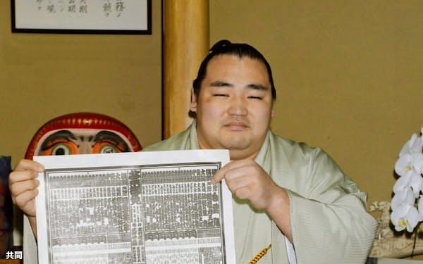 大相撲夏場所の新番付表を手にする新横綱鶴竜(24日午前、東京都墨田区の井筒部屋)=共同