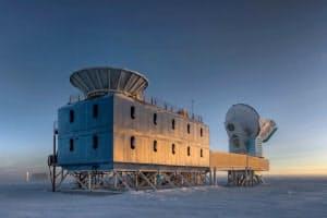 BICEP2望遠鏡は南極点から約800m離れた場所にある。写真は米アムンゼン・スコット基地のダークセクター実験棟と呼ばれる建物で,BICEP2は手前の建物の屋上,おわん形のシールドの中に置かれている。画面奥に見えるのは同じく原始重力波を探索している南極点望遠鏡(画像はSteffen Richter、 Harvard University提供)