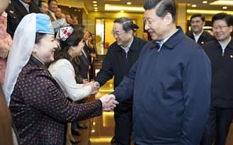 4月30日、中国新疆ウイグル自治区ウルムチを訪れ、地元の労働者らと握手する習近平国家主席(右)=新華社共同