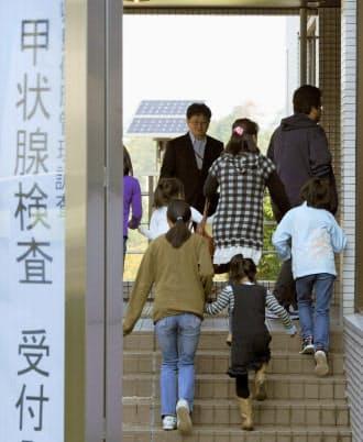 保護者に伴われ甲状腺の超音波検査に向かう子どもたち(2011年10月9日、福島市の県立医大病院)