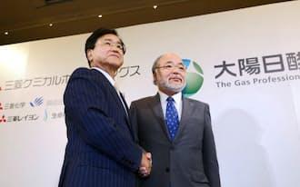 記者会見後、握手する三菱ケミカルホールディングスの小林社長(左)と大陽日酸の田辺社長(13日午後、東京都千代田区)
