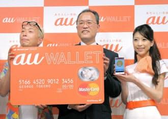 電子マネー「au WALLET(ウォレット)」を発表したKDDIの田中社長(中)。クレジットカードのようなカードを発行し、スマホの専用アプリなどで入金できるようにした(8日午後、東京都港区)