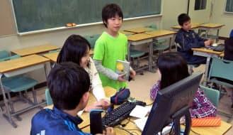 プログラミングを同級生にも教える中学1年生の山内くん(中央)