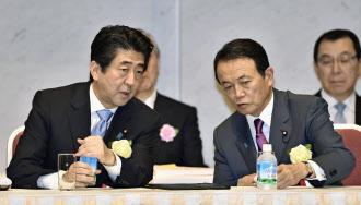 6月3日、経団連の定時総会で麻生副総理・財務相(右)と話す安倍首相=共同