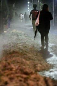 大量のひょうが積もった道を歩く人たち(24日夜、東京都調布市)
