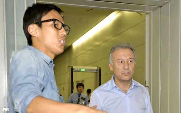 ザッケローニ監督が帰国。長谷部(左)に見送られ、羽田空港を出発するザッケローニ監督(1日)=共同