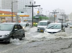 大雨の影響で冠水した道路を走る車(3日、長崎市)=共同