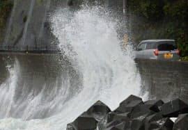 台風11号の影響で、県道を走る車の脇に打ち寄せる大波(9日、和歌山県串本町)=共同