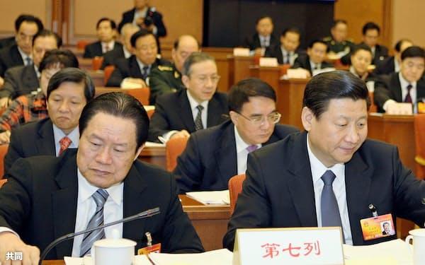2010年3月の中国全人代では、周永康氏(左)と習近平国家副主席(当時)は席を隣にして座っていた=共同