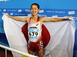 男子1万メートル競歩で優勝し、日の丸を掲げる小野川稔(24日、南京)=共同