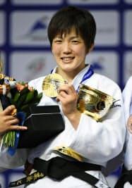 柔道の世界選手権女子57キロ級で初優勝し、笑顔で金メダルを掲げる宇高菜絵(27日、ロシア・チェリャビンスク)=共同