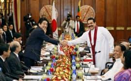会談を前に握手を交わすスリランカのラジャパクサ大統領(右)と安倍首相(7日、コロンボの大統領府)=共同