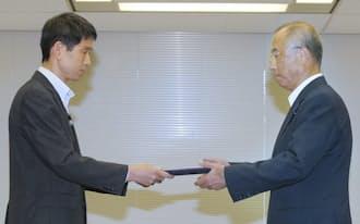 九州電力の中村上席執行役員(右)に「合格書」を手渡す原子力規制庁の市村安全規制管理官(10日午後、東京都港区)