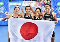 混合リレーで金メダルを獲得し、日の丸を手に喜ぶ(左から)佐藤、田山、上田、細田(26日、仁川)=共同