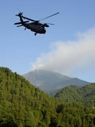 長野県警の警察官を乗せ、救助活動に向かう自衛隊のヘリコプター(29日午前、長野県王滝村)=共同