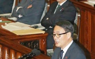 衆院本会議で質問する民主党の海江田代表。後方右は安倍首相(30日)