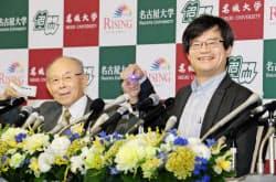 そろってノーベル物理学賞に決まり、記者会見で青色LEDを手に笑顔の天野氏(右)と赤崎氏(10日、名古屋大学)