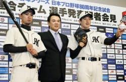 阪神と巨人の連合チームのユニホームでポーズをとる阪神・上本(左)と能見。中央は和田監督(21日、兵庫県西宮市)=共同