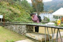 新潟県中越地震から10年を迎え「妙見メモリアルパーク」の献花台に花を供えて犠牲者の冥福を祈る女性(23日、新潟県小千谷市)=共同