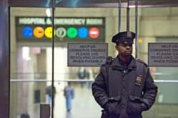 23日、米ニューヨークで、エボラ出血熱に陽性反応を示した男性医師が収容された病院の入り口で警戒する警官=ゲッティ共同