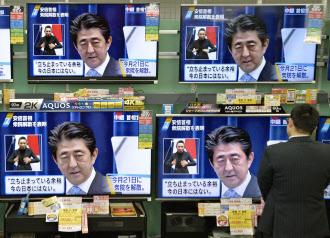 足を止めて安倍首相の会見模様に見入る人(18日夜、東京・新橋の家電量販店)=共同