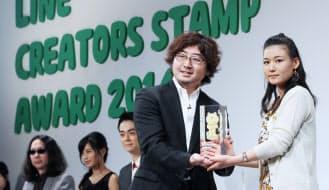 グランプリ受賞者の小嶋わにさん(右)にトロフィーを渡すLINEの森川社長(26日、東京都渋谷区)