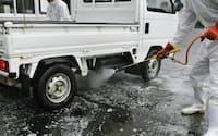 宮崎県川南町のJA事務所前で行われる車の消毒作業(19日午後)