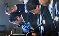 更生法申請の記者会見で頭を下げる武富士の経営陣(9月)
