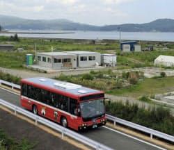 JR気仙沼線の線路跡地に敷かれたバス高速輸送システムの専用道を走るバス(17日、宮城県気仙沼市)