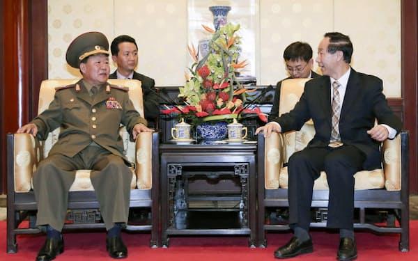 22日、北京で中国の王共産党中央対外連絡部長(右)と会談する朝鮮人民軍の崔総政治局長=新華社・共同