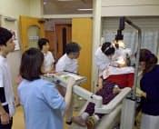 歯科医の診療には主治医や歯科衛生士、リハビリ担当者が立ち会い現場での情報交換も密にする(大分県由布市)