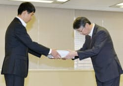 原子力規制庁に申請書を手渡す北海道電力の酒井副社長(右)(8日、東京都港区)