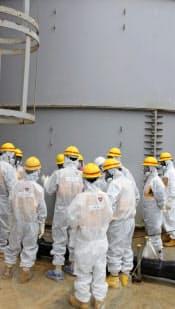 23日、福島第1原子力発電所で汚染水が漏れたタンクなどを視察する原子力規制委の委員ら