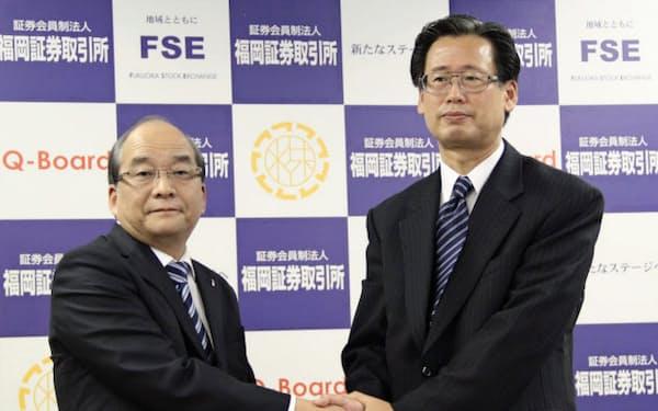 握手する西日本鉄道の倉富純男社長(左)とマルキョウの斉田敏夫社長(福岡市)