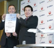 契約書を手にする日航の植木社長(右)とエアバスのブレジエCEO(7日、東京都港区)