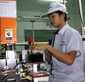 デジタルカメラなどに搭載する小型モーターの製造ラインで働くカンボジア人(ミネベアのカンボジア工場)