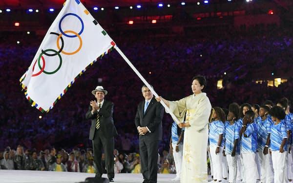五輪旗を持つ東京都の小池百合子知事。中央はIOCのバッハ会長=代表撮影